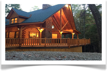 tall trees surronding two story lodge with 4 windows, wrap around deck